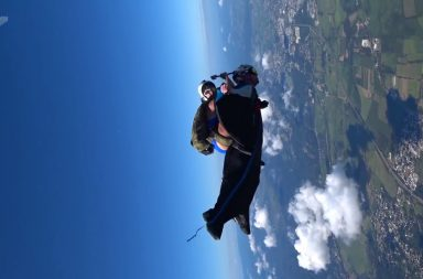 girl in bikini rides a guy in wingsuit